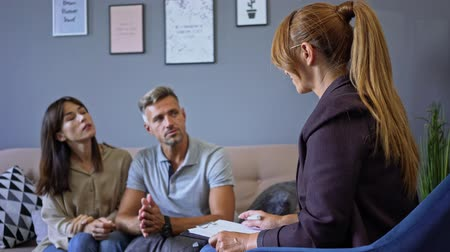 аргумент : Annoyed couple man and woman having conversation with psychologist on therapy session in room