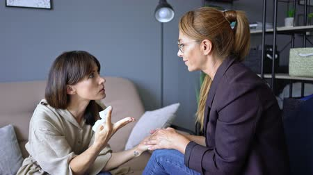 sofá : Unhappy vexed woman crying while having a conversation with a psychologist on therapy session in room