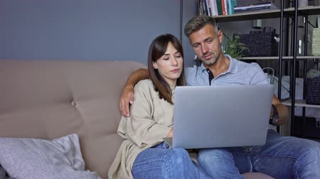 небритый : Cheerful couple man and woman smiling and speaking to each other while watching laptop on the sofa at home