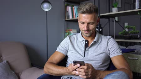 borotválatlan : Attractive man in casual clothing using his smartphone while resting at home