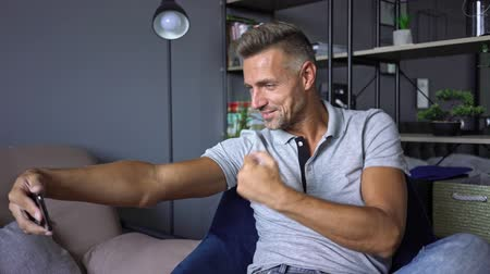 důvěra : A handsome strong man in casual clothing taking a selfie photo on his smartphone while resting at home