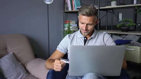 borotválatlan : Satisfied attractive man in casual clothing holding a credit card and a laptop while sitting on armchair in an apartment