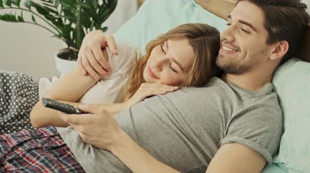abbracci : Cheerful couple man and woman lying together in bed and watching TV