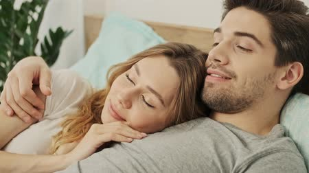 закрытыми глазами : Happy couple man and woman lying together in bed and dreaming