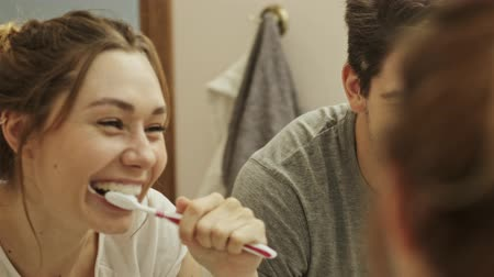 щеткой : Attractive couple having fun while cleaning teeth together in bathroom with brush and toothpaste