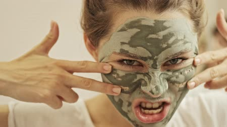 obličejový : Close up view of joyful young woman making funny facial expressions while standing in the bathroom with a green mask on her face