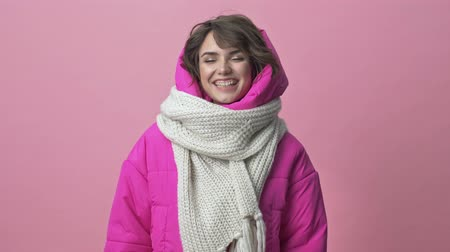 kısa : Beautiful young woman wearing winter jacket with a scarf smiling isolated over pink background Stok Video
