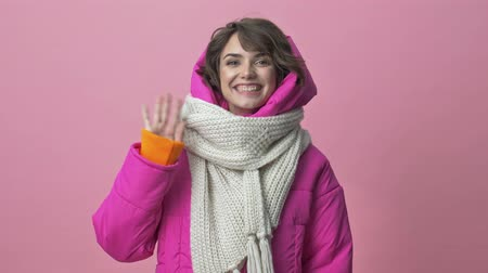 kıpkırmızı : Positive woman wearing a winter jacket with a scarf is doing a hello gesture while waving her hand isolated over a pink background