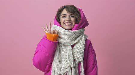 kısa : Happy young woman wearing a winter jacket with a scarf is doing OK gesture isolated over pink background