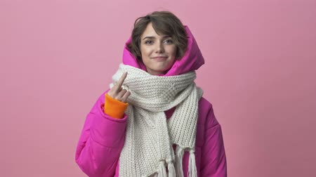 чертово : Attractive young woman wearing a winter jacket with a scarf is showing finger middle isolated over pink background Стоковые видеозаписи