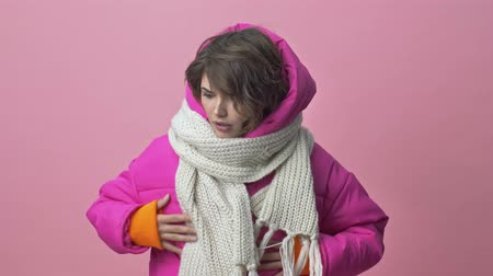 чертово : Nice young woman wearing a winter jacket with a scarf is looking for something in her pockets then showing a middle finger isolated over a pink background
