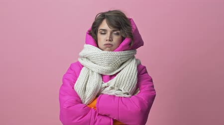kısa : Dissatisfied young woman wearing a winter jacket with a scarf is crossing her hands isolated over a pink background