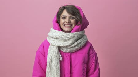 adorável : Happy positive young woman wearing a winter jacket with a scarf is nodding her head with a smile isolated over a pink background