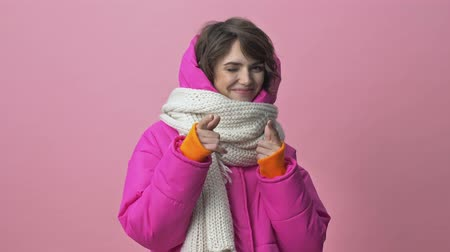 kısa : The positive young woman wearing a winter jacket with a scarf is pointing with two fingers to the camera isolated over a pink background Stok Video