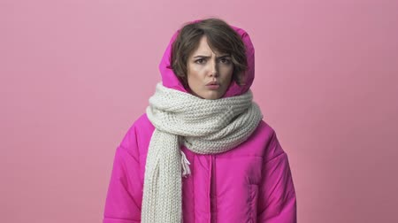 söylemek : Serious young woman wearing a winter jacket with a scarf is saying no and showing disagreement isolated over a pink background