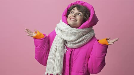adorável : Happy surprising young woman wearing a winter jacket with a scarf is looking up while throwing up hands isolated over a pink background Stock Footage