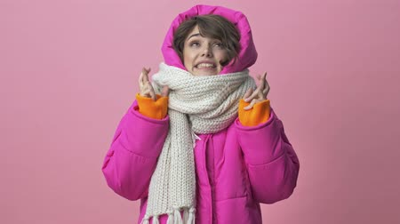 kısa : Beautiful young woman wearing a winter jacket with a scarf is crossing her fingers isolated over a pink background Stok Video