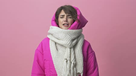 kıpkırmızı : Nice young woman wearing a winter jacket with a scarf is sneezing isolated over a pink background