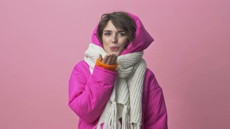 sturen : Cute young woman wearing a winter jacket with a scarf is sending an air kiss to the camera isolated over a pink background