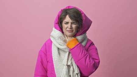 crimson : Sick young woman wearing a winter jacket with a scarf is having a sore throat isolated over a pink background Stock Footage