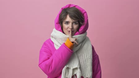 kıpkırmızı : Good looking young woman wearing a winter jacket with a scarf is doing a silence gesture isolated over a pink background Stok Video