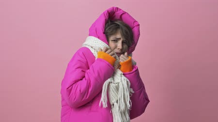 kısa : Nice young woman wearing a winter jacket with a scarf is scaring of something isolated over a pink background