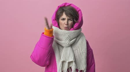 bufanda : Pretty young woman wearing a winter jacket with a scarf is feeling a stink isolated over a pink background
