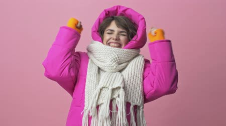 kıpkırmızı : Happy young woman wearing a winter jacket with a scarf is doing a winner gesture isolated over a pink background