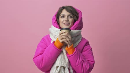 kısa : Beautiful young woman wearing a winter jacket with a scarf is drinking a cup of tea or coffee in craft paper cups isolated over a pink background