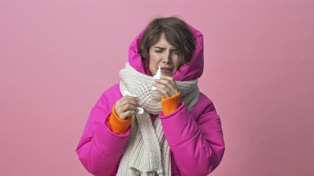 dokular : A sick woman wearing a winter jacket with a scarf is holding a paper napkin and dripping nose isolated over a pink background