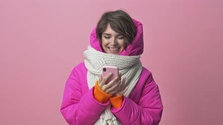 クリムゾン : Attractive young woman wearing a winter jacket with a scarf is using a smartphone isolated over a pink background 動画素材
