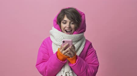 kısa : Surprising positive young woman wearing a winter jacket with a scarf is holding a smartphone while looking to the camera isolated over a pink background