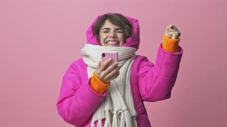 クリムゾン : Happy surprising young woman wearing a winter jacket with a scarf is doing a winner gesture while holding a smartphone isolated over a pink background 動画素材