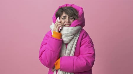 bufanda : Frozen young woman wearing a winter jacket with a scarf is calling on the smartphone isolated over a pink background Archivo de Video