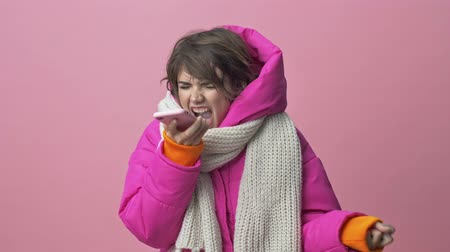 kısa : Angry young woman wearing a winter jacket with a scarf is screaming on her smartphone while having a call isolated over a pink background Stok Video