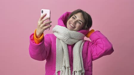 kıpkırmızı : Joyful young woman wearing a winter jacket with a scarf is doing a selfie isolated over a pink background Stok Video