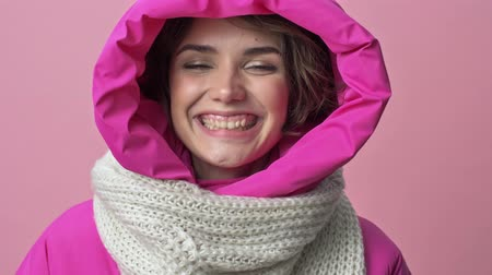 kıpkırmızı : Close up view of pretty young woman wearing a winter jacket with a hood is smiling to the camera isolated over a pink background