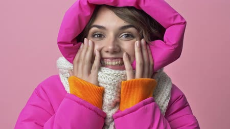 kısa : Close up view of  happy surprised young woman wearing a winter jacket with a hood is touching her cheeks while smiling isolated over a pink background