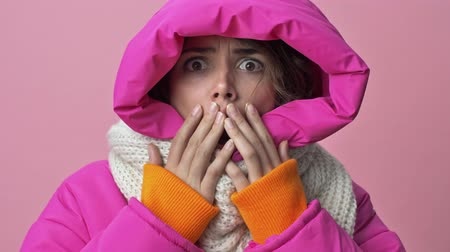прическа : Close up view of beautiful young woman wearing a winter jacket with a hood is scaring of something isolated over a pink background