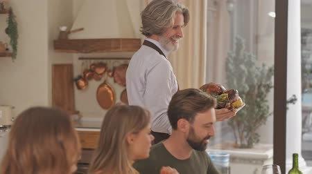 kaczki : Happy elderly man in apron bringing a baked duck to the table on festive family dinner at home