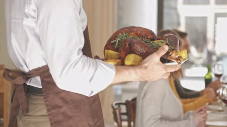 молодой взрослый человек : Cropped view of elderly man in apron holding baked duck while standing near the table on festive family dinner at home Стоковые видеозаписи