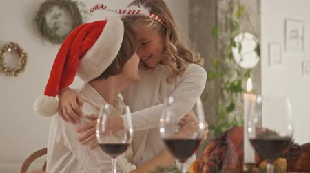 chifre : Satisfied mother with daughter wearing in christmas outfit having fun together and hugging each other on festive family dinner by the table
