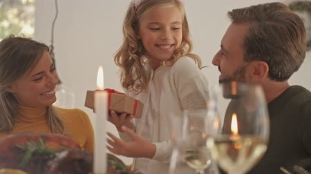 růžky : Happy blonde young girl receiving a gift and enjoying while standing near the table with her parents on festive family dinner