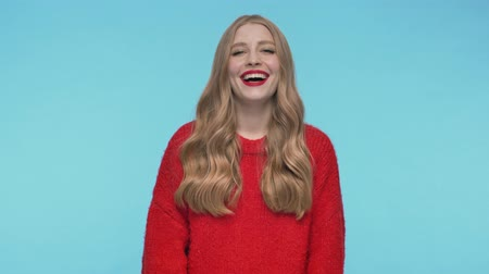 embarrassed : Happy pretty woman in sweater laughing and looking at the camera over turquoise background Stock Footage