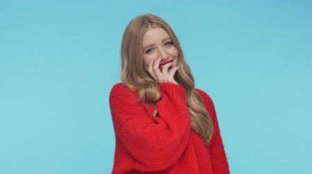 embarrassed : Cheerful pretty woman in sweater laughing and covering her mouth while looking at the camera over turquoise background Stock Footage