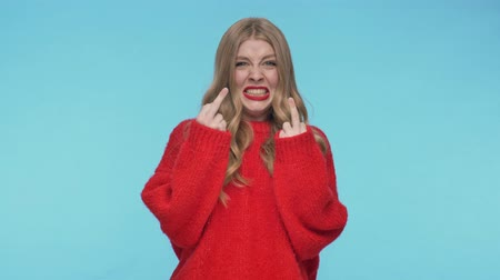 embarrassed : Angry pretty woman in sweater showing middle fingers while looking at the camera over turquoise background Stock Footage