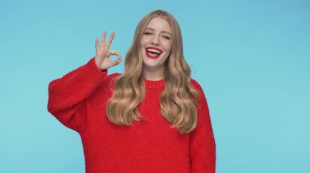 embarrassed : Joyful pretty woman in sweater showing ok gesture and looking at the camera over turquoise background