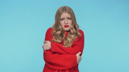 embarrassed : Upset pretty woman in sweater having cold over turquoise background Stock Footage