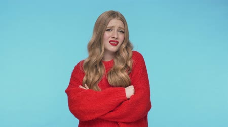 head over : Upset displeased pretty woman in sweater posing with crossed arms and looking around over turquoise background
