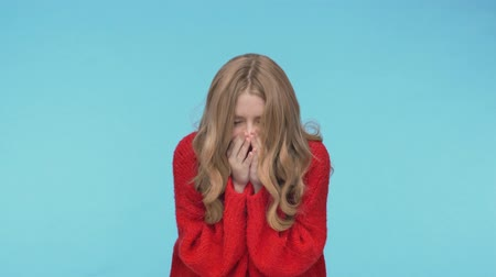 смущенный : Young pretty woman in sweater having runny nose and sneezing over turquoise background Стоковые видеозаписи